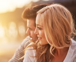 pretty girl cuddling with boyfriend on beach at santa monica